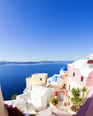 ia: blue dome churches and classic cyclades architecture over the mediterranean sea in oia santorini the famous greek island