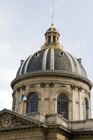 academie: dome and cupola detail of the institute of france (institut de france) in paris france with the french national flag