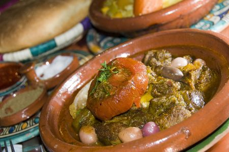 authentic lamb tagine stewed meat food with fruits and vegetables and spice tray with moroccan bread as photographed in casablance morocco africa
