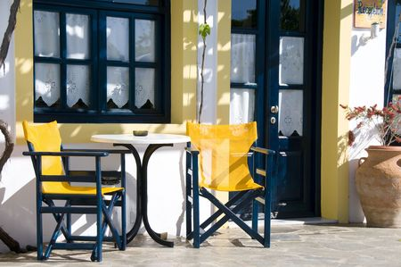 cafe taverna and hotel setting with table and chairs and grape vines in the greek islands photo