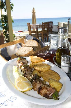 crusty: greek island taverna restaurant specialty  pork souvlaki shish kebob with home made wine and crusty bread in greece