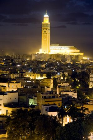 the largest: Hassan II mosque night scene at dusk sundown with lights overlooking the Atlantic Ocean in Casablanca Morocco Africa which is the largest mosque in Morocco and the third largest mosque in the world