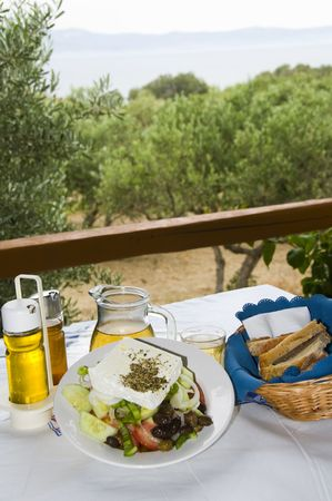 aegean: carafe of home made house and greek salad with feta cheese at greek island taverna with view of aegean sea and island of naxos with crusty local bread photographed in paros cyclades greek islands
