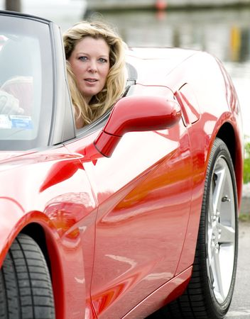 top down car: sexy woman smiling driving hot red convertible sports car  Stock Photo