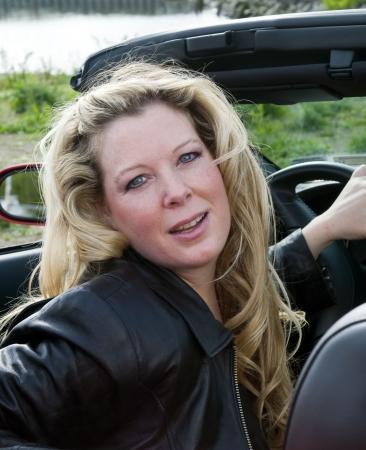 セクシーな女性の川熱いコンバーチブルのスポーツカー フロントに笑みを浮かべて