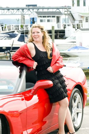 sexy woman smiling with hot red convertible sports car in front of yacht club boats on river Stock Photo