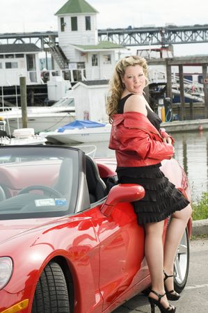 top down car: sexy woman smiling with hot red convertible sports car in front of yacht club boats on river Stock Photo
