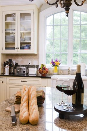 luxury home modern custom kitchen with wine and baguettes on center island photo