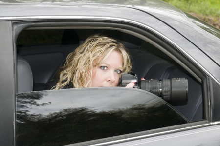 private investigator: attractive secret agent undercover police woman or investigator spying with a long telephoto lens camera from a darkened window car Stock Photo