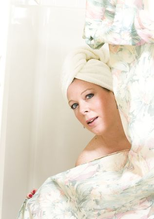 pretty middle age woman drying hair with towel while standing in shower