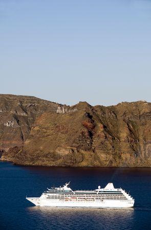travler: passenger cruise ship entering harbor while passing the volcanic islands in the caldera of santorini greek island