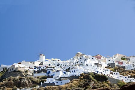 cycladic: the famous town of oia ia santorini built into the caldera volcanic cliffs over the mediterranean sea as seen from amoudi port in the cyclade greek islands