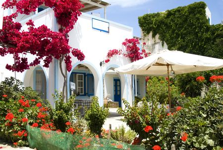 cyclades: whitewashed greek island antiparos architecture  hotel with arches and blue shutters and rails common to the greece cyclades islands with beautiful spring flowers