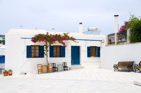 outdoor cafe setting with typical greek furniture chairs and generic architecture in the greek islands village of lefkes paros cyclades island greece Archivio Fotografico