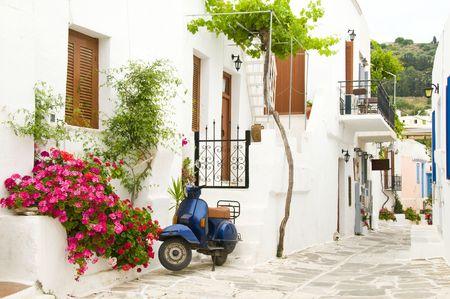 白塗りの建物の重い木製のシャッターとモーター スクーター、花、典型的なキクラデス島の建築のストリート シーンを描いた、ギリシャの島々 の