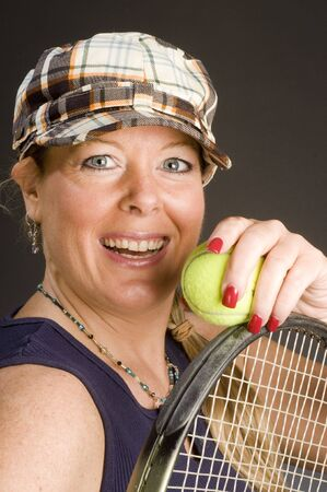retro woman: happy smiling middle age woman tennis player with racquet and ball wearing retro fashion tennis hat