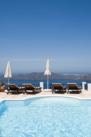swimming pool at luxury resort overlooking the volcanic islands and caldera of famous santorini in the greek island town of imerovigli near oia photo