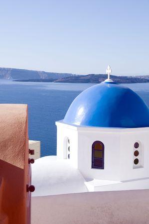 青いドーム教会と古典的なキクラデス建築サントリーニ島イアの地中海で有名なギリシャの島 写真素材