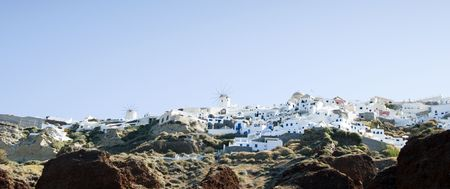 fira: panoramic view of the famous town of oia ia santorini with classic cyclades architecture built into the caldera volcanic cliffs over the mediterranean sea as seen from amoudi port in the cyclade greek islands