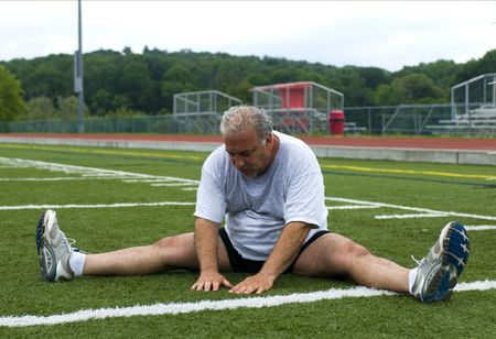 overweight middle age senior man stretching his muscles after exercising on sports field