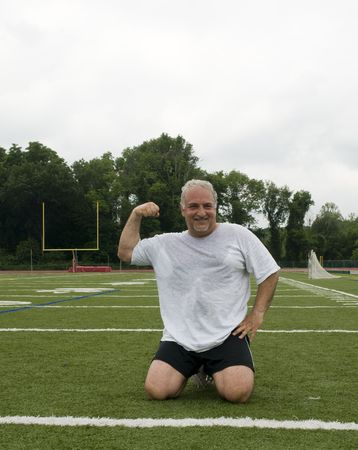 overweight middle age senior man stretching his muscles  and flexing his biceps for fitness and healthy lifestyle image photo
