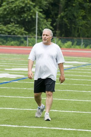 pancia grassa: mezza et� in sovrappeso alti uomo esercita sul campo sportivo Archivio Fotografico