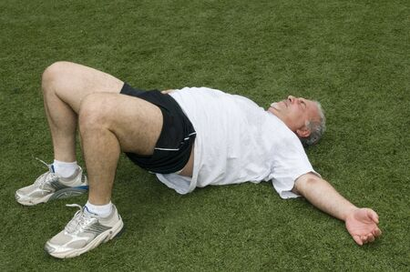 overweight middle age retired and active senior man stretching his back muscles after exercising on a sports field outdoors photo