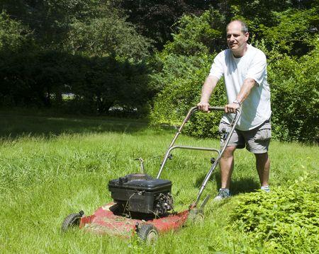 gras maaien: knap middelbare leeftijd man snijden overgroeid met gras ouderwetse grasmaaier op voorstedelijk huis