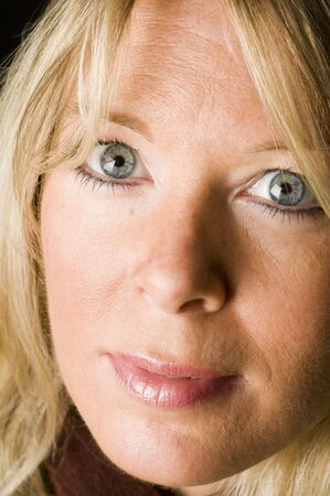 attractive middle age woman with blond hair and big blue eyes posing for a head shot portrait photo