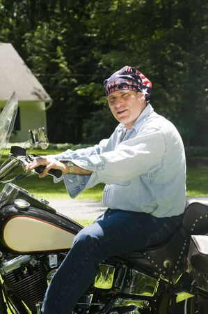 patriotic middle age senior man on large motorcycle at suburban house wearing American flag bandana on head Imagens