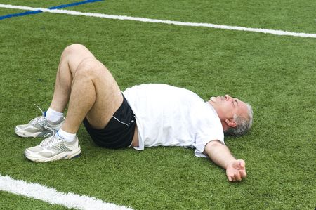 overweight middle age retired and active senior man stretching his leg muscles after exercising on a sports field outdoors