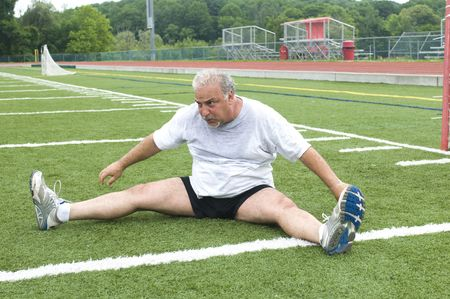 overweight middle age retired and active senior man stretching his leg muscles after exercising on a sports field outdoors photo