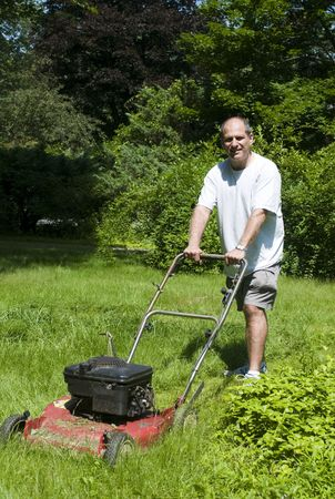 handsome middle age man cutting overgrown grass with old fashioned lawn mower at suburban house photo