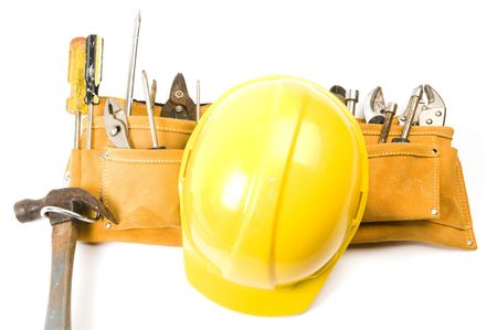 a suede leather contractors construction mans tool belt with assorted tools and a yellow protective hard hat helmet