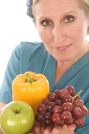 pretty nurse or or medical professional wearing nurse's scrub clothes and offering healthy food with colorful bell pepper vegetables and fruits
