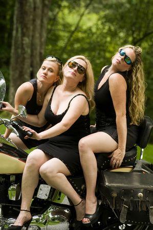 郊外の背景を持つ大規模なバイクに中年のブロンドの女性のセクシーなグループ