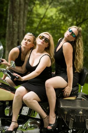 sexy group of middle age blond women on large motorcycle with suburban background Stock fotó