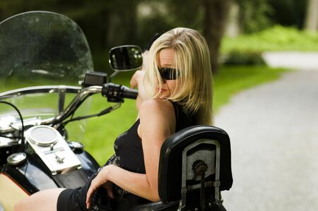 sexy blond woman on large motorcycle  with suburban background photo