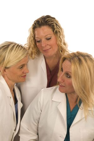group of three pretty nurses or s or medical professionals wearing nurse's scrub clothes and lab coats conferring with positive outlook