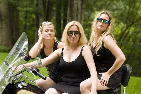 sexy group of middle age blond women on large motorcycle with suburban background Stock Photo