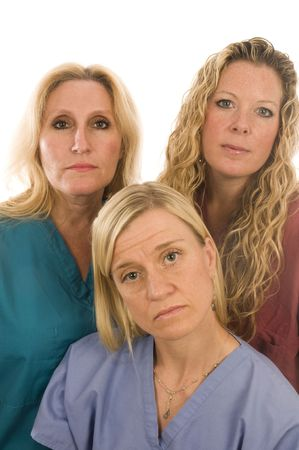 group of three pretty nurses or s or medical professionals wearing nurse's scrub clothes with serious expression on faces