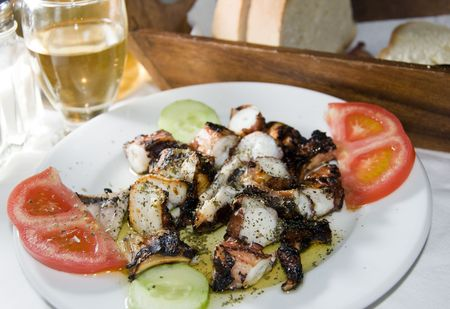 greek island taverna restaurant specialty food of marinated grilled octopus with crusty bread and glass of homemade house wine as photographed on the island of santorini photo