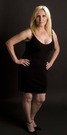 middle age glamorous blond woman posing in low cut little black cocktail dress in photo studio Stock Photo