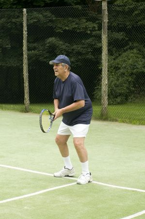 actively: overweight senior man actively playing tennis on private club tennis court