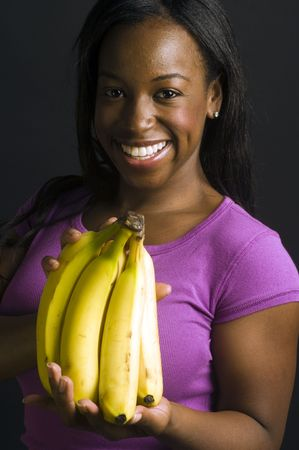 portrait of smiling happy pretty sexy young latin puerto rican black woman with fresh fruit bananas bunch photo