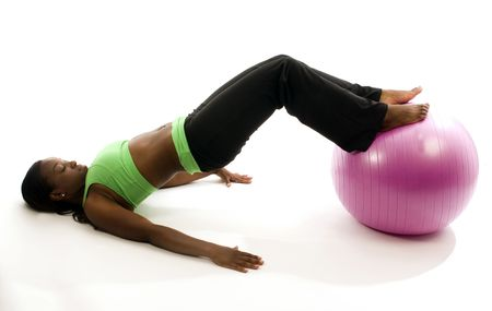 young and pretty hispanic latina black woman wearing exercise tights and working out sit ups with fitness core ball photo