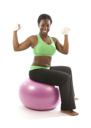 young and pretty hispanic latina black woman wearing exercise tights and working out lifting dumbell weights with fitness core ball photo