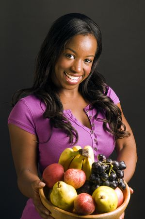 pretty latina hispanic african american woman smiling and offering bowl of healthy fresh fruit  photo