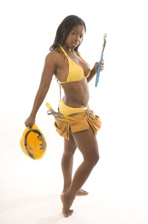bikini construction: young and pretty hispanic latina black woman wearing bikini swim suit and working construction with tools and hard hat helmet Stock Photo