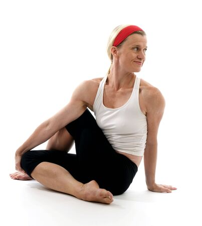 yoga spine twisting pose illustrated by attractive middle age fitness trainer teacher woman exercising and stretching